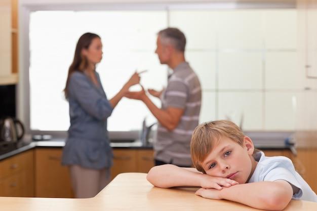 Trauriger kleiner junge, der sein argumentierendes elternteil hört