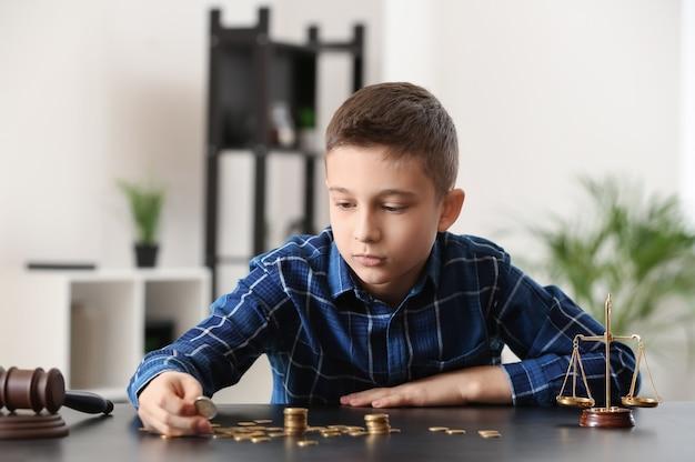 Trauriger kleiner junge mit münzen, die am tisch in der anwaltskanzlei sitzen.
