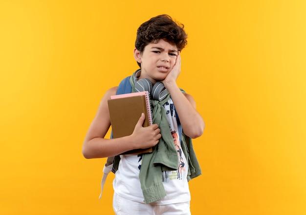 Trauriger kleiner schuljunge, der rückentasche und kopfhörer trägt, die bücher halten und hand auf wange lokalisiert auf gelb setzen