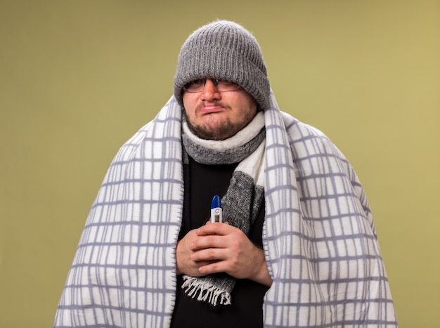 Trauriger kranker mann mittleren alters mit wintermütze und schal, eingewickelt in kariertes thermometer, isoliert auf olivgrüner wand