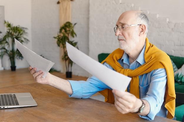 Trauriger männlicher ingenieur in den sechzigern, der formelle kleidung und brille trägt und mit einem generischen laptop am holzschreibtisch sitzt, dokumente in den händen hält und frustriert ist. job-, berufs- und stresskonzept