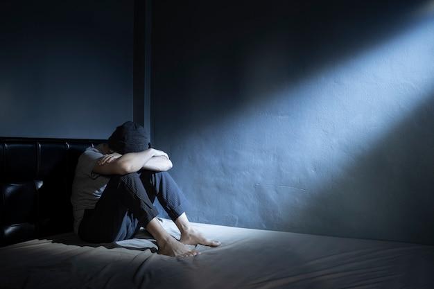 Trauriger mann auf dem bett in der dunkelkammer