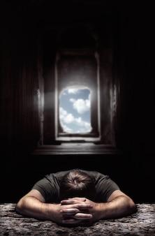 Trauriger mann auf dem tisch gegen das licht am ende