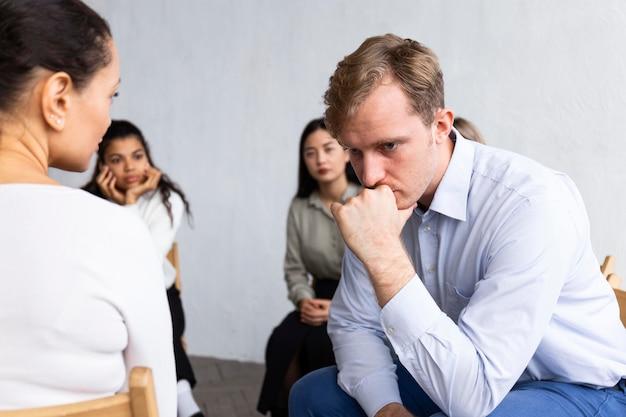 Trauriger mann bei einer gruppentherapiesitzung
