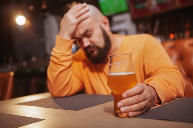 Trauriger mann, der allein in der bierkneipe trinkt.