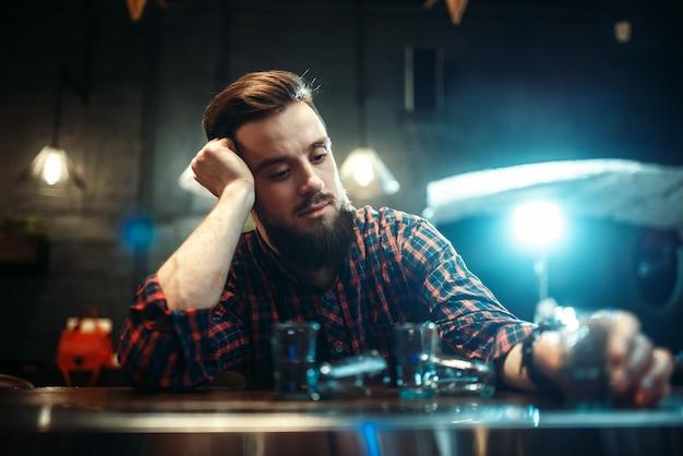 Trauriger mann, der am bartheke sitzt, alkoholabhängigkeit