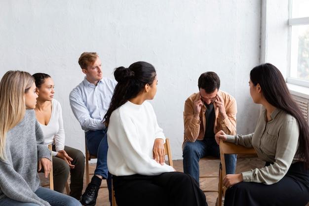 Trauriger mann, der bei einer gruppentherapiesitzung über seine probleme spricht