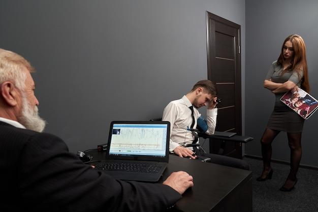 Trauriger mann, der fragen während des lügendetektortests beantwortet