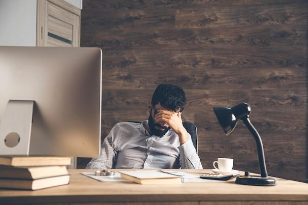 Trauriger mann, der im büro sitzt