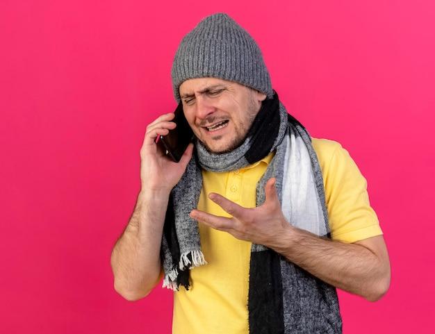 Trauriger mann, der wintermütze und schal warnt, spricht am telefon auf rosa