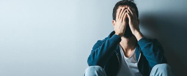 Trauriger mann hand in gesicht, das im boden sitzt