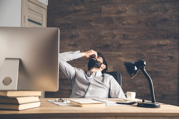 Trauriger mann hand in nase im büro