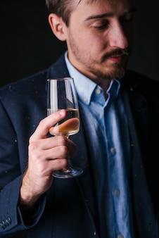 Trauriger mann im blau, das in der hand mit champagnerglas steht