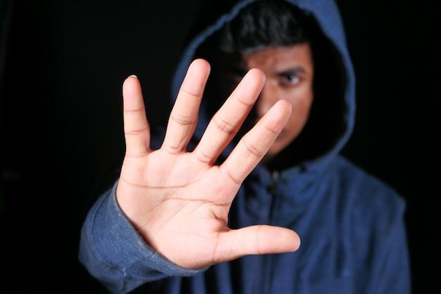 Trauriger mann im haubenabdeckungsgesicht mit den in schwarz lokalisierten händen