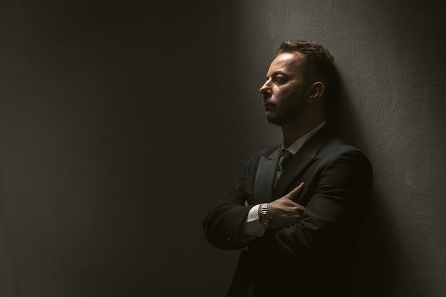Trauriger mann im schwarzen anzug an der schwarzen wand