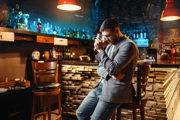 Trauriger mann mit glas des alkoholischen getränks am hölzernen bartheke. müder kunde in der kneipe, männliche person entspannen im restaurant