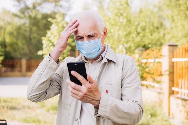 Trauriger mann mit medizinischer gesichtsmaske, die das telefon benutzt, um nach nachrichten zu suchen