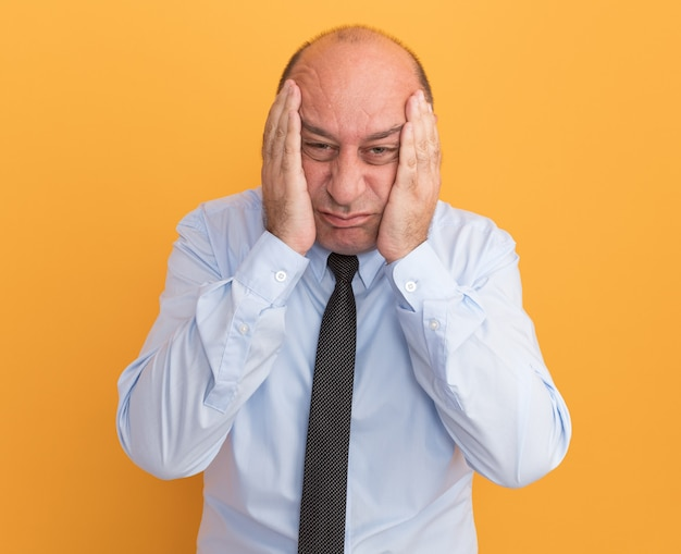Trauriger mann mittleren alters, der weißes t-shirt mit krawatte bedeckt wangen mit händen auf orange wand isoliert