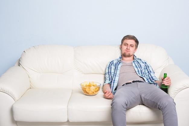 Trauriger mann oder fußballfan, der fußball im fernsehen sieht