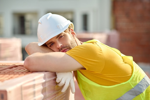 Trauriger müder baumeister in einem schutzhelm, der sich nach harter arbeit ausruht