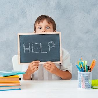 Trauriger müder frustrierter schuljunge am tisch und hält papier mit worthilfe. lernschwierigkeiten, bildungskonzept