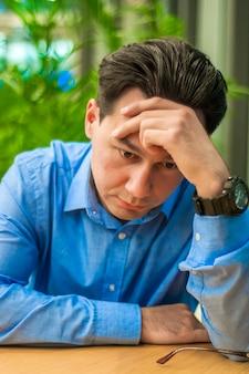 Trauriger, müder oder depressiver geschäftsmann am schreibtisch. geschäftsmann mit problemen und stress im büro
