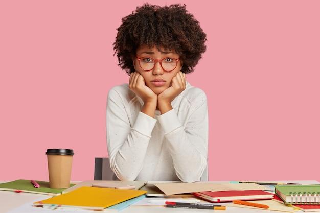 Trauriger mürrischer student mit lockigem buschigem haar, hält die hände unter dem kinn, trägt eine optische brille, sieht unglücklich aus