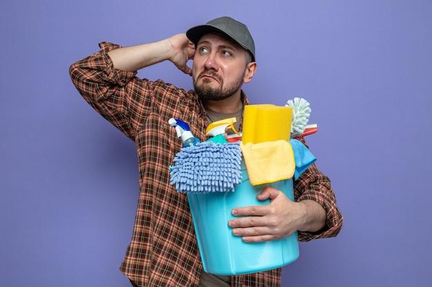 Trauriger reinigungsmann, der reinigungsgeräte hält und die hand auf den kopf legt und zur seite schaut