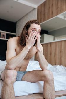 Trauriger schläfriger junger mann, der am morgen auf dem bett sitzt