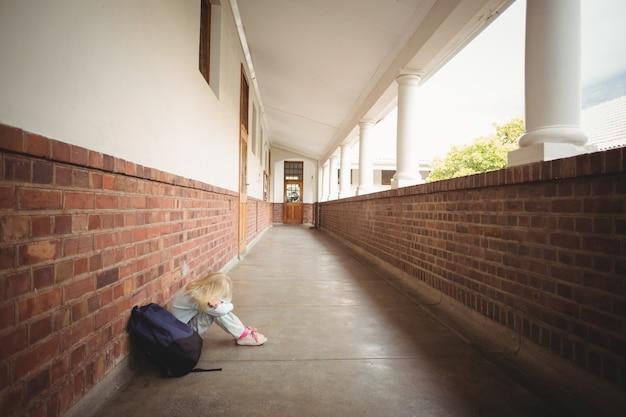 Trauriger schüler, der alleine auf dem boden sitzt