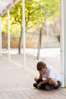 Trauriger schüler, der alleine im flur sitzt