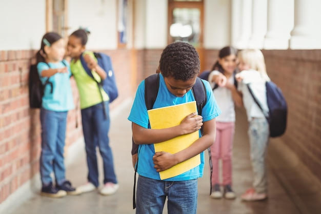 Trauriger schüler, der von klassenkameraden am korridor schikaniert wird