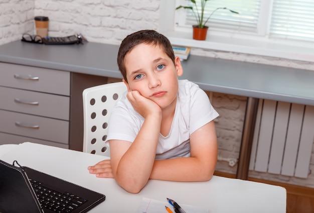 Trauriger schuljunge, der allein am schreibtisch zu hause sitzt. mürrischer unzufriedener junge