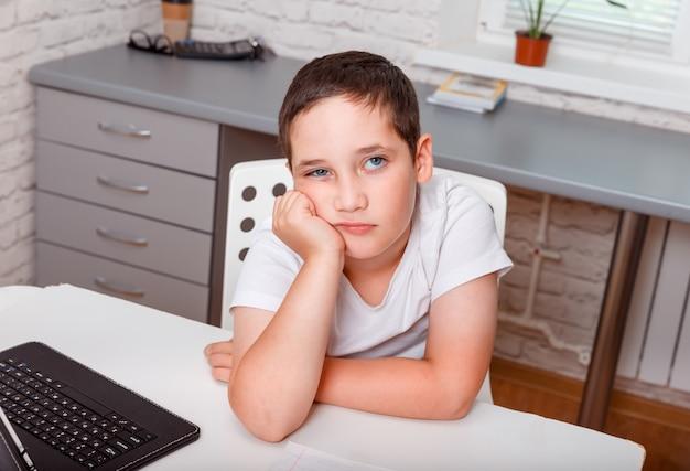 Trauriger schuljunge, der allein am schreibtisch zu hause sitzt. mürrischer unzufriedener kleiner junge im weißen t-shirt mit gerunzelter stirn, unzufrieden mit unfairer schulnote
