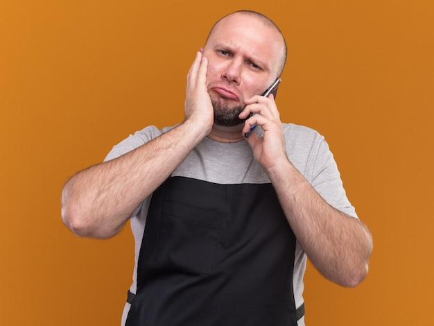 Trauriger slawischer männlicher friseur mittleren alters in uniform spricht am telefon und legt die hand auf die wange, die auf der orangefarbenen wand isoliert ist