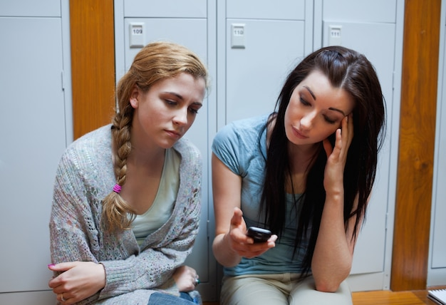 Trauriger student, der ihrem freund eine textnachricht zeigt