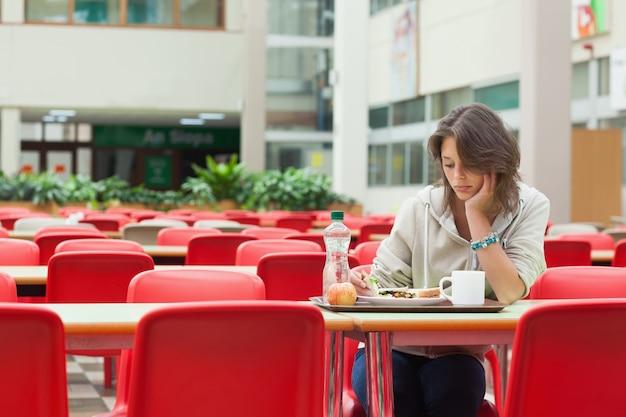 Trauriger student in der cafeteria mit essenstablett