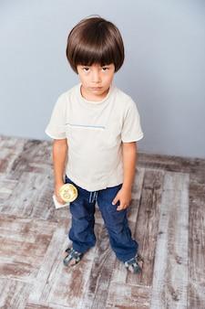 Trauriger süßer kleiner junge, der die pokaltrophäe steht und hält