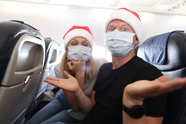 Trauriger und betrunkener mann und frau in medizinischen schutzmasken und roten weihnachtsmützen, die im flugzeug fliegen