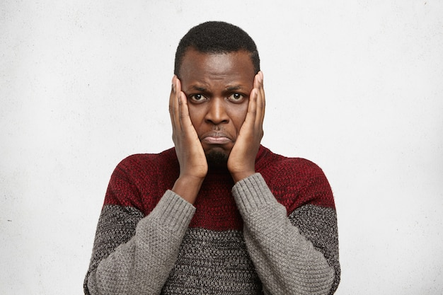 Trauriger und depressiver junger dunkelhäutiger mann, der hände auf wangen hält und starrt, nachdem er einen schmerzhaften blick betont hat und unter starken zahnschmerzen leidet. menschliche mimik, emotionen und gefühle