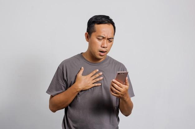 Trauriger und enttäuschter asiatischer mann bekommt schlechte nachrichten vom smartphone