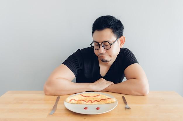 Trauriger und langweiliger mann isst selbst gemachten frühstückssatz omelett.