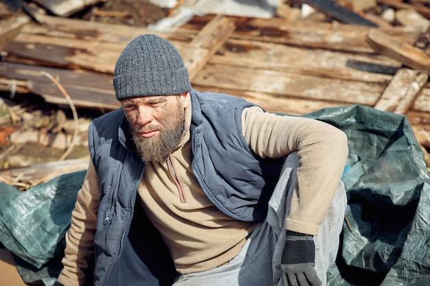 Trauriger und verärgerter obdachloser und arbeitsloser in den ruinen