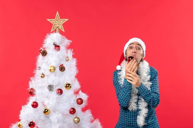 Trauriger unglücklicher emotionaler junger mann mit weihnachtsmannhut in einem blauen gestreiften hemd und in der dekoration haltend