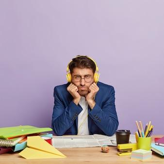 Trauriger unzufriedener geschäftsmann, der am schreibtisch sitzt
