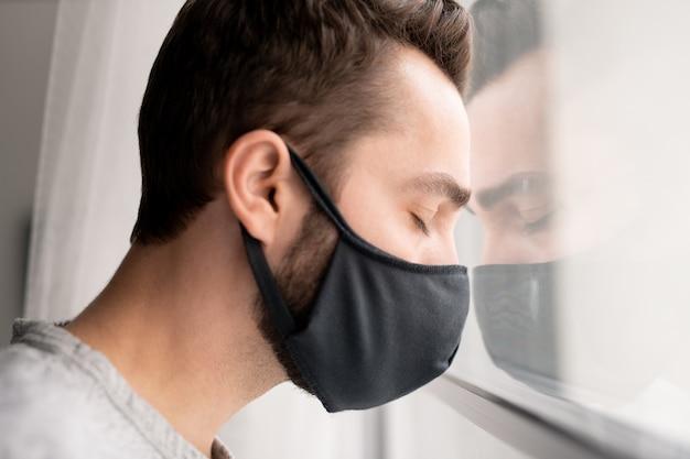 Trauriger verwirrter junger mann in der stoffmaske, der kopf auf fenster lehnt und augen geschlossen hält, während depression wegen der isolierung des coronavirus fühlt