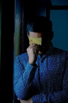 Trauriger verwirrter und gestresster mann, der kreditkarten hält.
