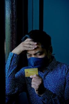Trauriger verwirrter und gestresster mann, der kreditkarten mit tragender gesichtsmaske hält.