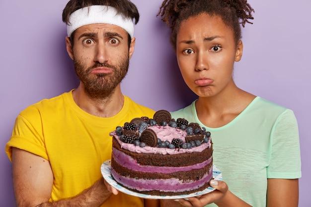Trauriges aktives paar, das mit einem großen kuchen aufwirft