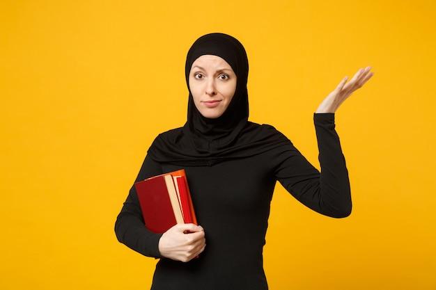 Trauriges arabisches muslimisches studentenmädchen in schwarzer hijab-kleidung hält bücher isoliert auf gelbem wandporträt. menschen religiöser lebensstil, bildung im high-school-konzept. .